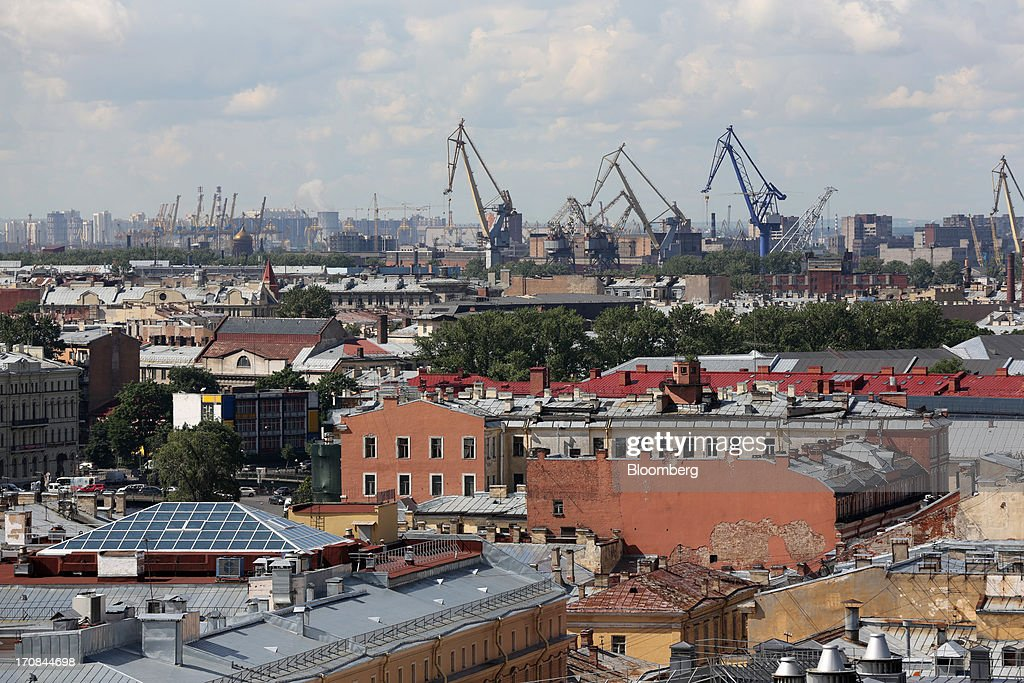 Cranes stand in the commercial port area beyond city buildings ahead of the St. Petersburg International Economic Forum 2013 (SPIEF) in St. Petersburg, Russia, on Wednesday, June 19, 2013. The Russian Deputy Prime Minister Igor Shuvalov told the conference that the country's World Trade Organization accession negotiations could be further delayed unless several remaining disputed matters are solved. Photographer: Andrey Rudakov/Bloomberg via Getty Images