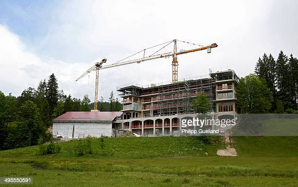 Cranes stand next to the construction site of a new wing at Schloss Elmau, a luxury spa hotel, in the Bavarian Alps of southern Germany on June 3,...