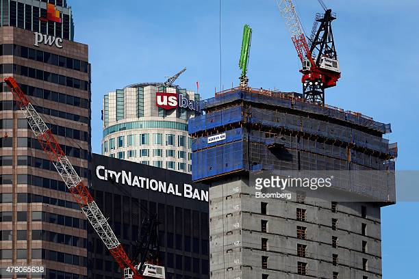 Cranes stand on the new Korean Air Lines Co building which will rise higher than the US Bank Library Tower rear during its construction in downtown...