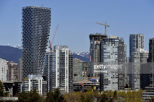 Cranes stand over residential buildings including the Vancouver House left in Vancouver British Columbia Canada on Thursday April 16 2020 As its oil...