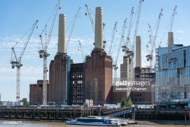 cranes surround battersea power station, london, seen from across the river thames. - wandsworth stock pictures, royalty-free photos & images