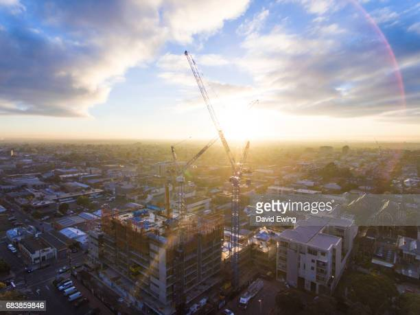 cranes tower over a new construction site at sunrise in brunswick, melbourne. - david ewing stock pictures, royalty-free photos & images