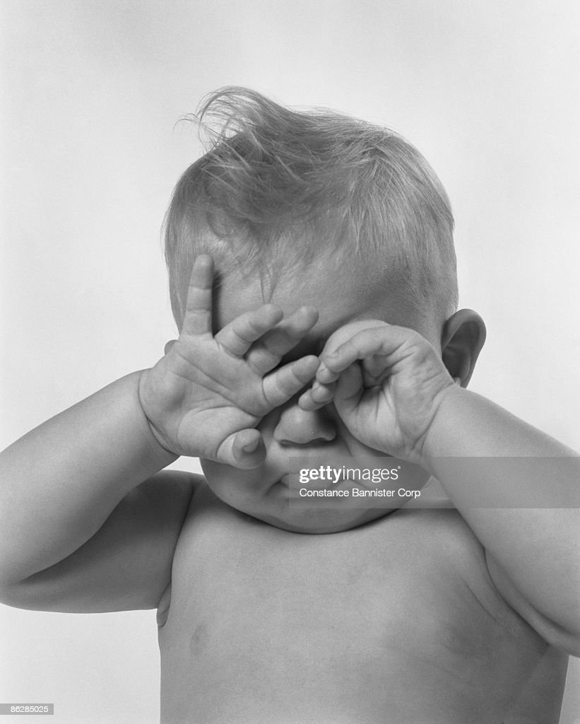 Cranky baby covering eyes : Stock Photo