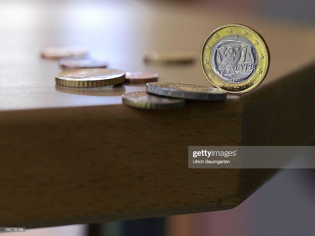 BONN, 'Crash?' - Greek 1 euro coin on a table edge.