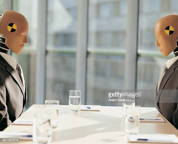 Crash Test Dummies Sitting Face to Face Behind Desks