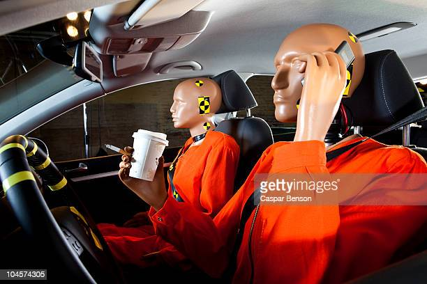 A crash test dummy carelessly using a mobile phone while driving with a crash test dummy passenger