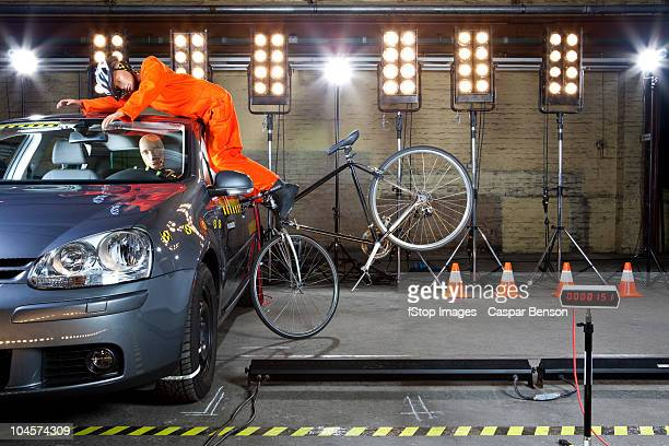 A crash test dummy on a bicycle crashing into a car