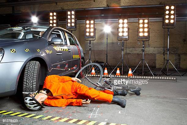 A crash test dummy on ground after bicycle crashed