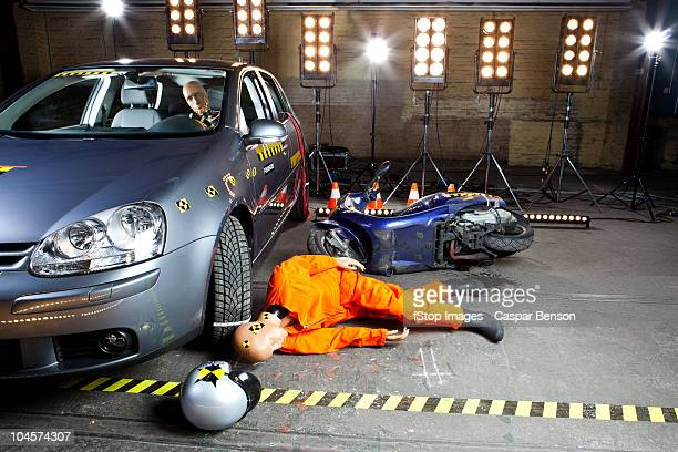 A crash test dummy on ground after scooter crashed into car