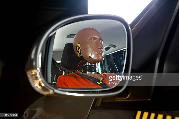 A crash test dummy reflected in a side-view mirror