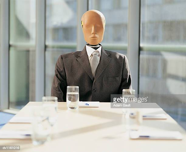 Crash Test Dummy Sitting Behind a Desk in a Meeting Room