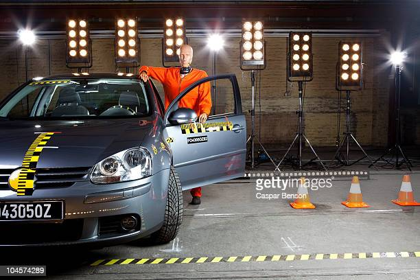 A crash test dummy standing by a car and leaning on it