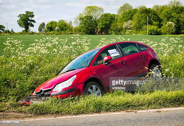 crashed car in a ditch - ditch stock photos and pictures