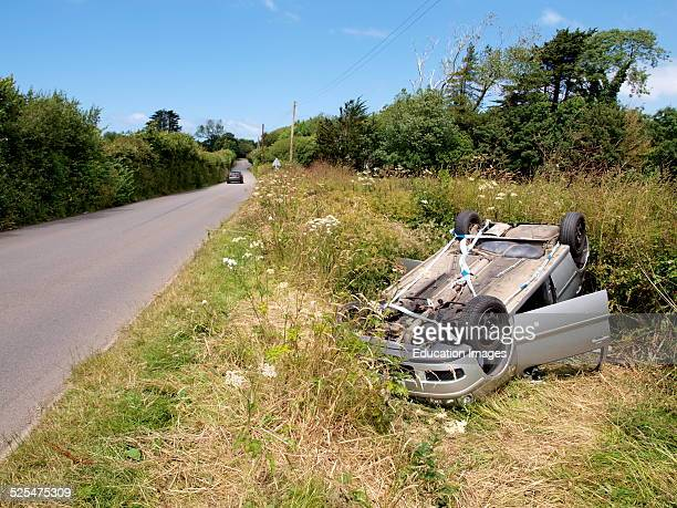Crashed car upside down in a ditch beside the road Westward Ho Devon UK