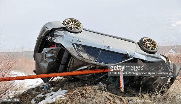 Crashed car upside down on side of road