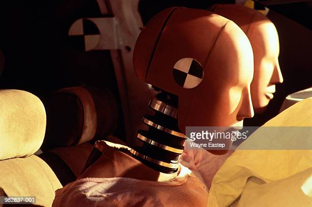 Crash-test dummies inside car with inflated airbags, close-up