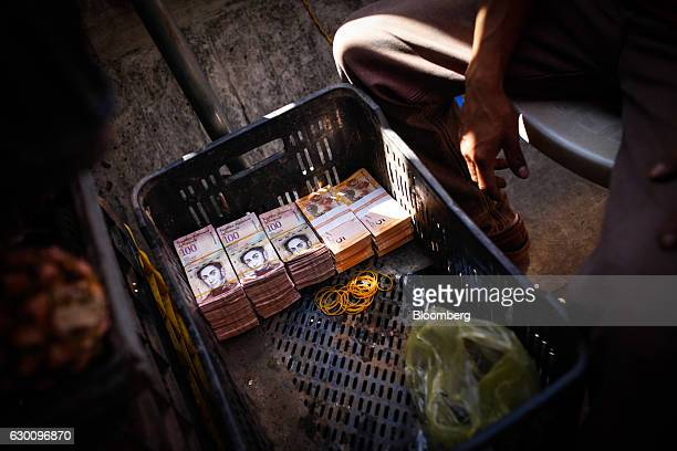 A crate containing 100 and 50bolivar notes sits at a fruit stand in Caracas Venezuela on Friday Dec 16 2016 The largest denomination of Venezuela's...