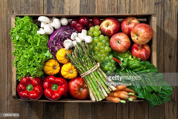 Crate full of fruits and vegetables over rustic table