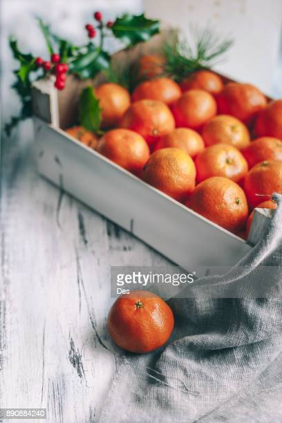 crate of satsumas decorated with a sprig of holly - zitrusfrucht stock-fotos und bilder