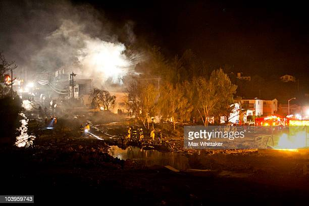 A crater filled with water marks the site of an explosion that caused a fire the massive fire burning in a residential neighborhood September 9 2010...