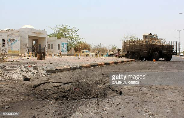 A crater is seen in the ground as Yemeni government forces walk in Zinjibar the capital of the southern Abyan province on August 16 2016 following an...