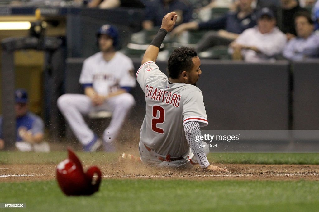 J.P. Crawford #2 of the Philadelphia Phillies slides into home plate to score a run in the sixth inning against the Milwaukee Brewers at Miller Park on June 15, 2018 in Milwaukee, Wisconsin.