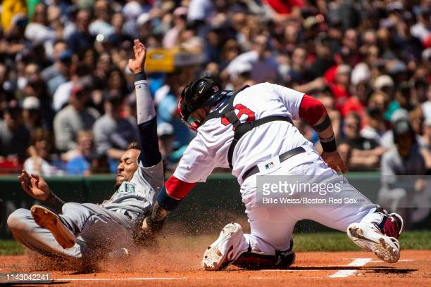 P Crawford of the Seattle Mariners slides as he avoids the tag of Sandy Leon of the Boston Red Sox to score during the first inning of a game on May...