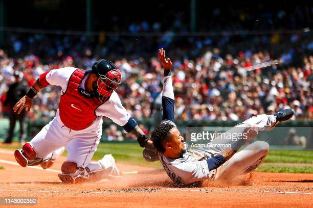 P Crawford of the Seattle Mariners slides safely into home plate past the tag of Sandy Leon of the Boston Red Sox in the first inning of a game at...