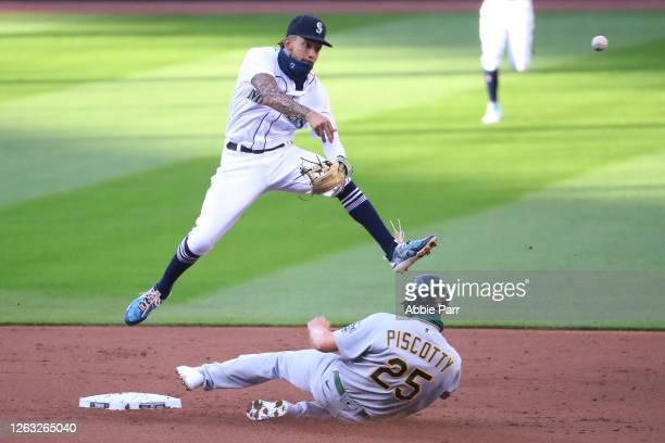 Crawford of the Seattle Mariners throws to first base for a double play after outing Stephen Piscotty of the Oakland Athletics in the third inning...