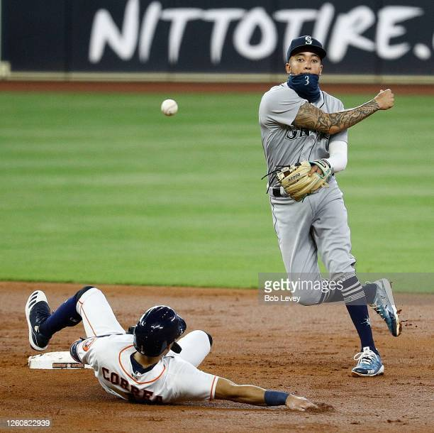 Crawford of the Seattle Mariners throws to first base over Carlos Correa of the Houston Astros to complete a double play in the second inning at...