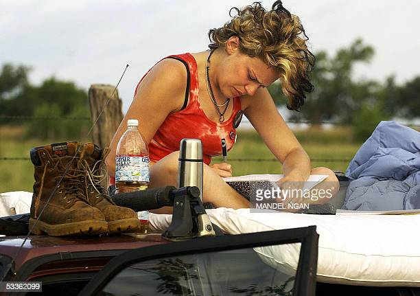 Diane Morse of San Francisco California sits ontop of a car on the side of a country road 12 August near the ranch of US President George W Bush in...