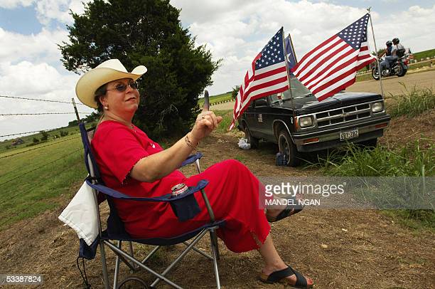 Diane Wallin a supporter of US President George W Bush holds up her finger stained with green ink at passing motorists near the makeshift camp of...