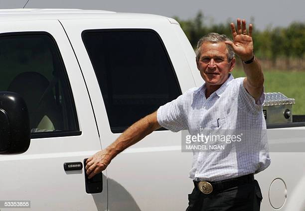 US President George W Bush waves as he reaches to open the door of his truck at the conclusion of a press conference 11 August 2005 after a meeting...