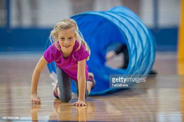 crawling out of a tunnel - school gymnastics stock photos and pictures