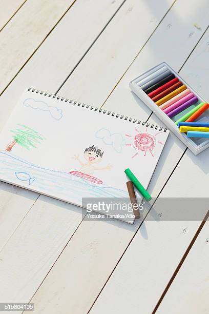 Crayons and drawing on white wooden flooring