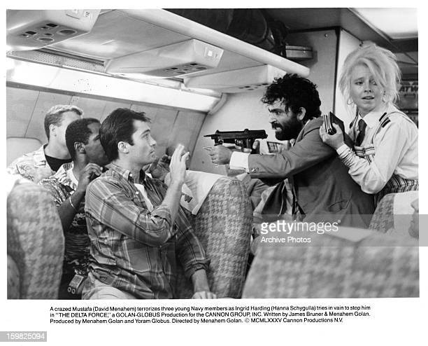 A crazed David Menahem terrorizes three young Navy members as Hanna Schygulla tries in vain to stop him in a scene from the film 'The Delta Force'...