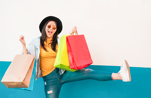 Crazy fashion Asian girl doing shopping in mall center - Happy Chinese woman having fun buying new clothes - Consumerism, people and youth lifestyle concept 1129960744