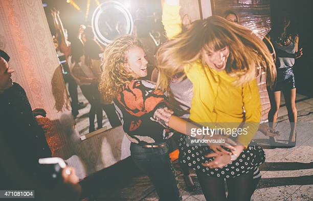 Crazy friends dancing wildly at a party in a club