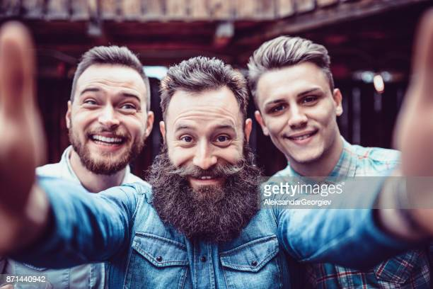 crazy guys at pub drinking beer and taking selfie - facial hair stock pictures, royalty-free photos & images