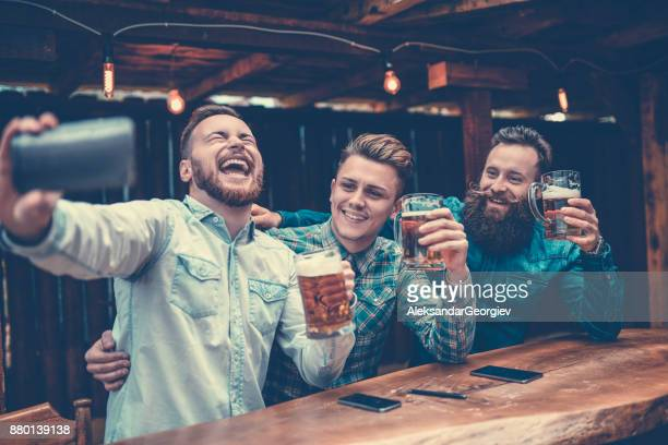 Crazy Guys at Pub Drinking Beer and Taking Selfie