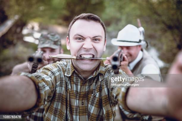 verrückte hunter mit messer in seinem mund machen selfie mit freund in den wald - überleben stock-fotos und bilder