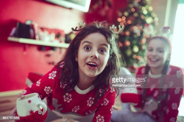 Verrückte kleine Schwestern unter dem Weihnachtsbaum sitzen und trinken heiße Getränke