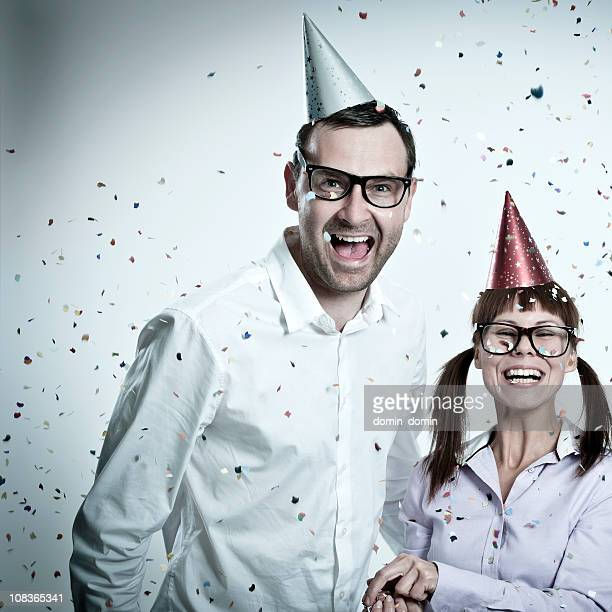 Crazy party geek couple toothy smiling, party hats, confetti