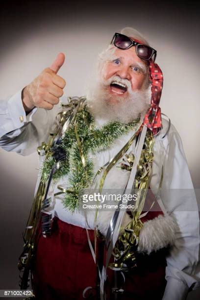 Crazy Santa Claus on a party with thumbs up
