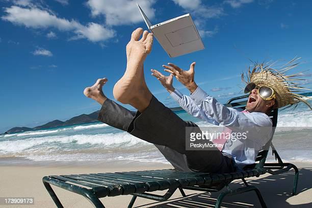 Homme d'affaires fou touristiques jetés de son ordinateur portable sur la plage tropicale
