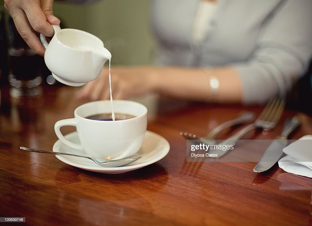 Cream being poured into cup of coffee : Stock Photo