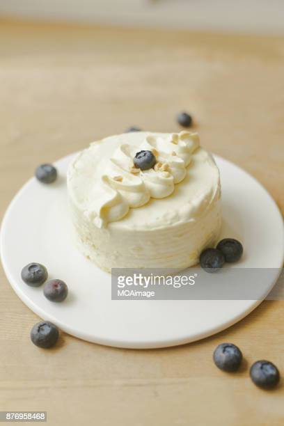 a cream cake with some blueberries on wooden table - 盛り皿 ストックフォトと画像