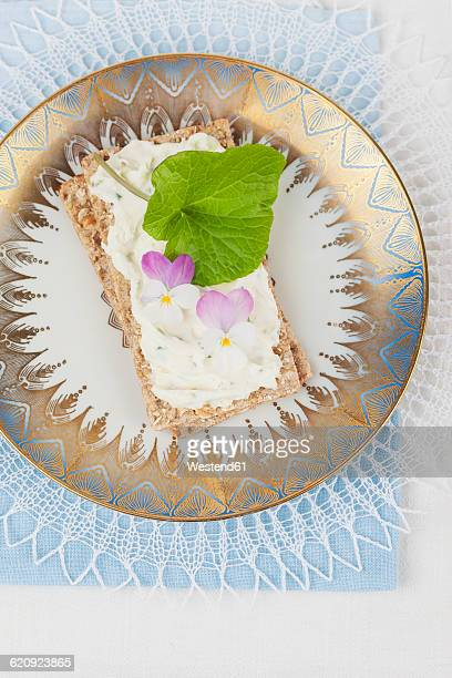 Cream cheese with violet and wasabi on crispbread, eatable blossoms