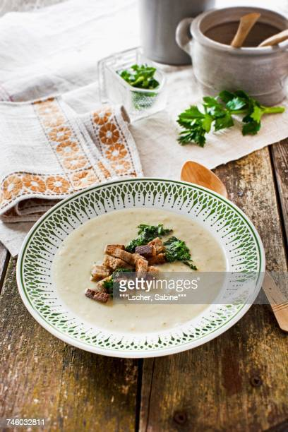 Cream of celery soup garnished with black bread croutons and fried celery leaves