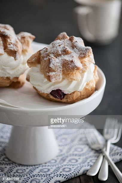 Cream puffs filled with whipped cream and sour cherries on cake stand